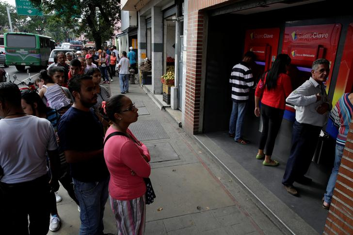 People line up to withdraw cash from an automated teller machine (ATM) outside a Banco de Venezuela branch in Caracas, Venezuela November 25, 2016. Picture taken November 25, 2016.