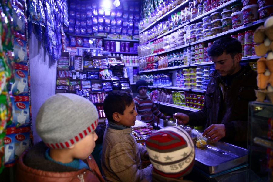 Boys buy goods from a grocery shop in the rebel-held, besieged Damascus suburb of Eastern Ghouta, Syria, Feb. 12, 2017.