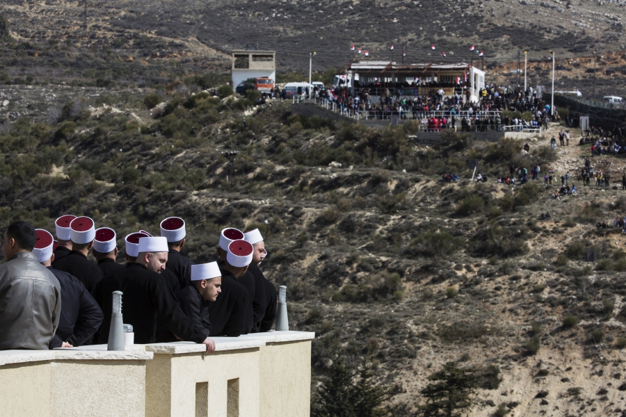 Members of the Druze community look at their friends and relatives on the Syrian side of the border, during a rally in the Druze village of Majdal Shams on the Israel-occupied Golan Heights, Feb. 14, 2014.
