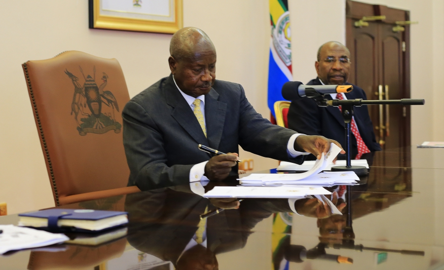 Uganda's President Yoweri Museveni signs an anti-gay bill into law at the state house in Entebbe, southwest of the capital Kampala, Feb. 24, 2014.