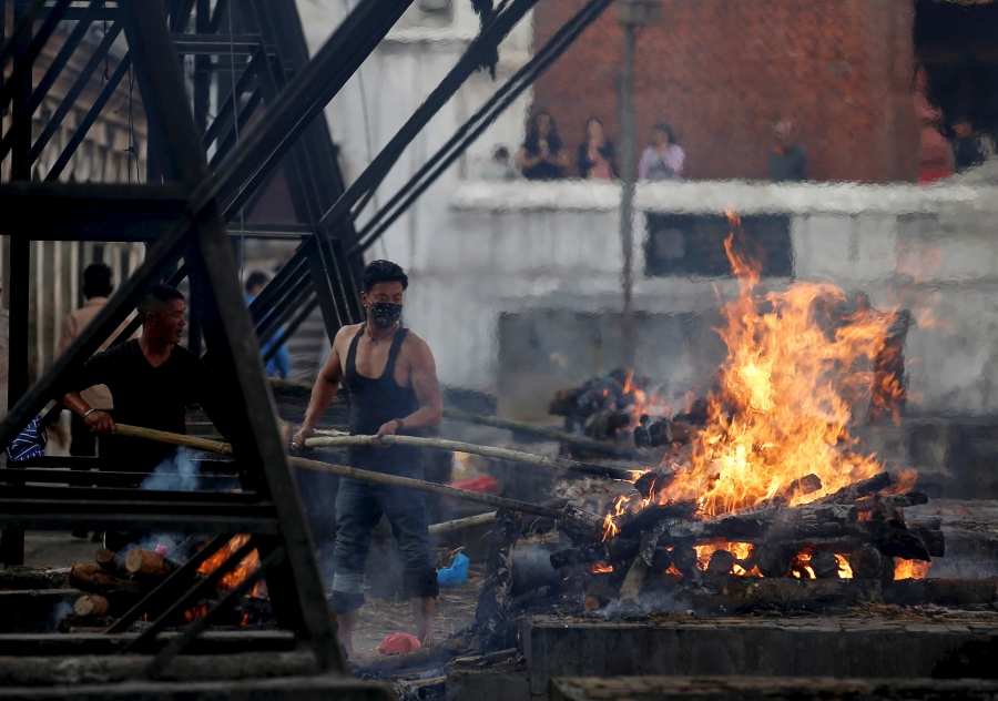 Worker tends cremation fires
