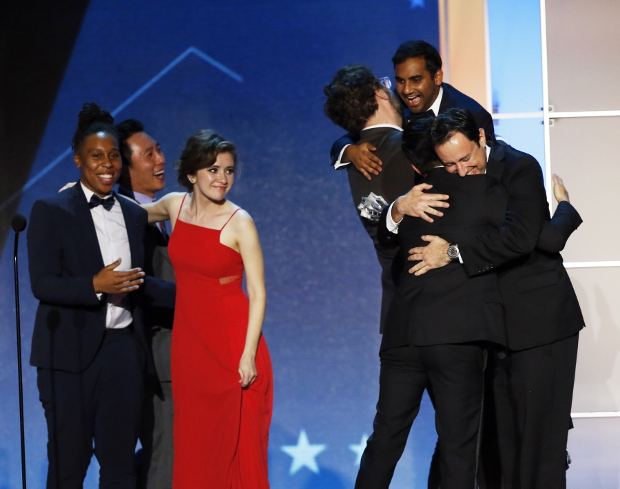 Group on stage hugging, with Ansari lifted up