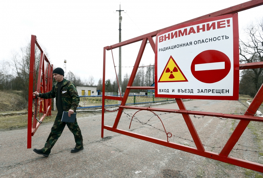 An employee opens the gate at a checkpoint in the exclusion zone around the Chernobyl nuclear reactor. After the April 26, 1986 accident, roughly 350,000 people were relocated from the zone.