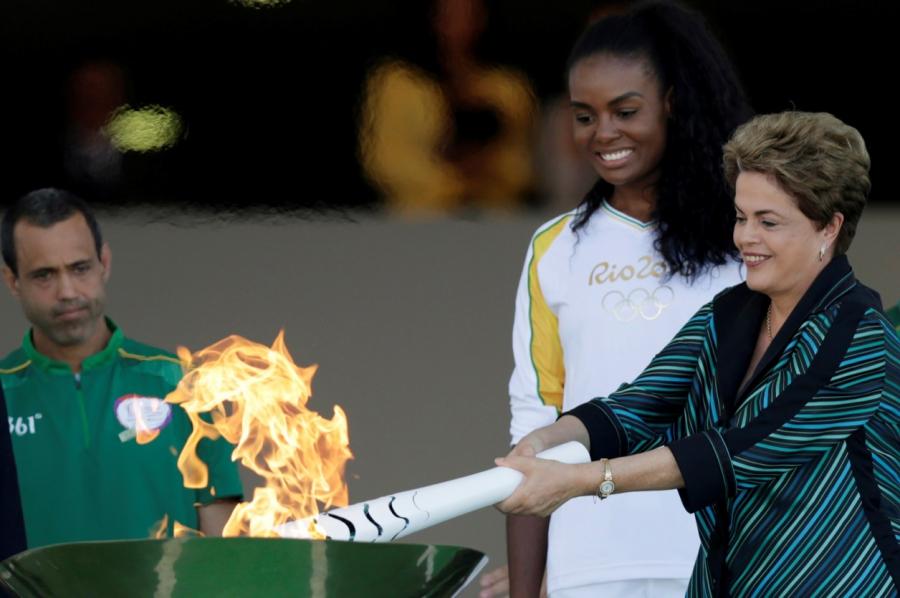 Brazil's President Dilma Rousseff lights a cauldron with the Olympic Flame