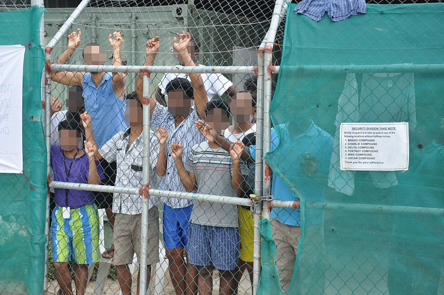 Asylum-seekers look through a fence at the Manus Island immigration detention camp on Papua New Guinea. Manus Island is one of two offshore detention camps funded by the Australian government to house migrants intercepted at sea. Some of the asylum seeker