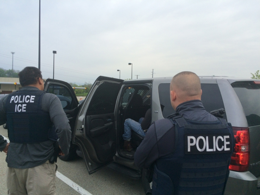 Agents with vests placing a man in car