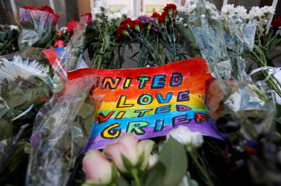 A placard and flowers for the victims of the shooting at a gay nightclub in Orlando are seen in front of the U.S. Embassy in Moscow, Russia, June 13, 2016.
