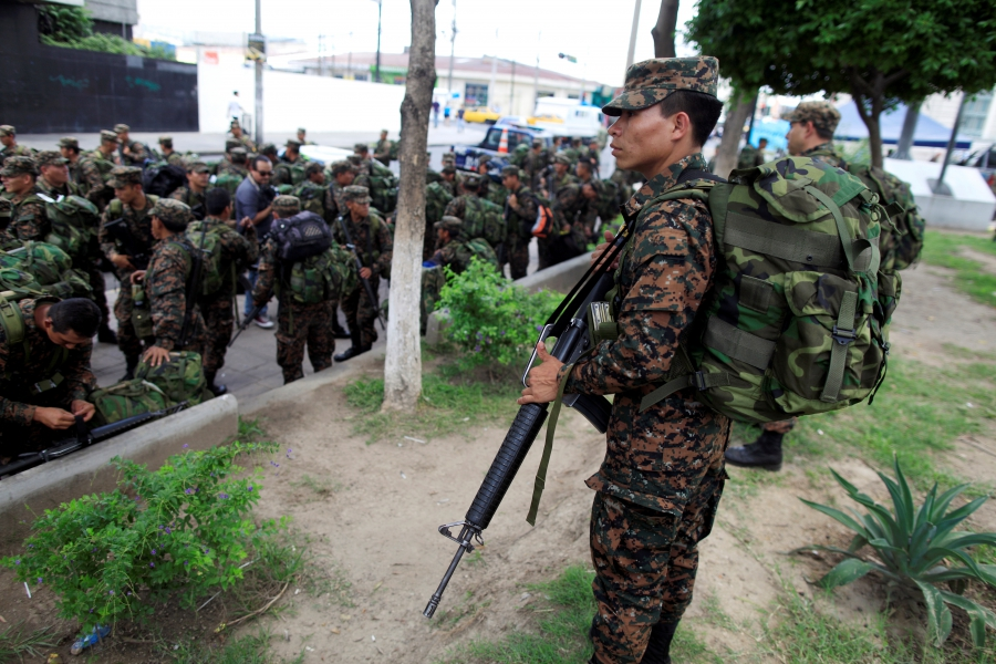 Salvadoran army reserve soldiers wait to board trucks after an official ceremony prior to their deployment to deal with gang violence in San Salvador,
