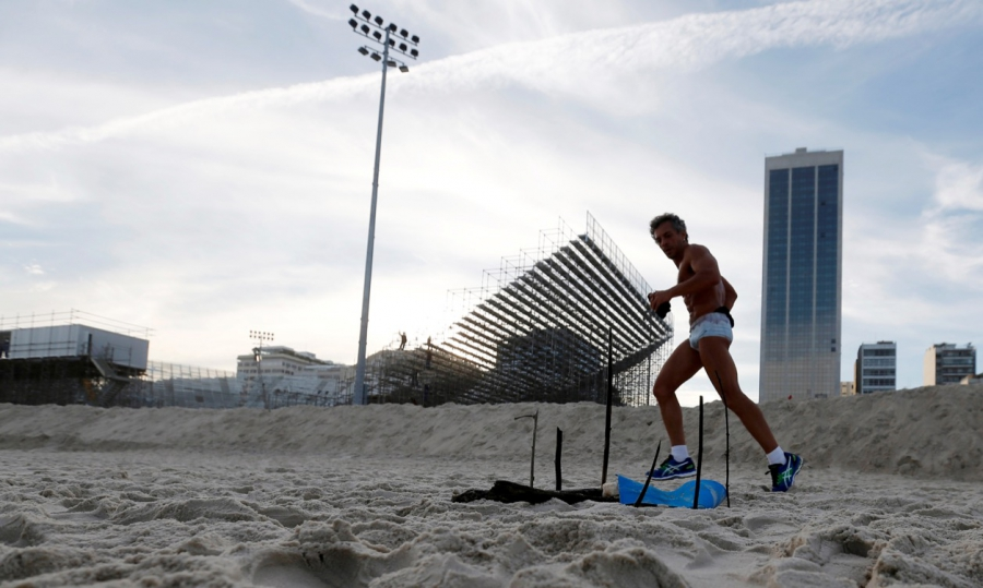 A man runs near a mutilated body part near the construction site of the beach volleyball venue for the 2016 Rio Olympics on Copacabana beach, on June 29.