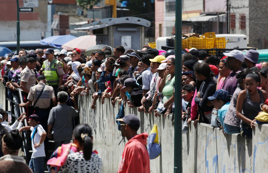 People gather to buy food and other staple goods outside a supermarket in Caracas, Venezuela June 30, 2016.