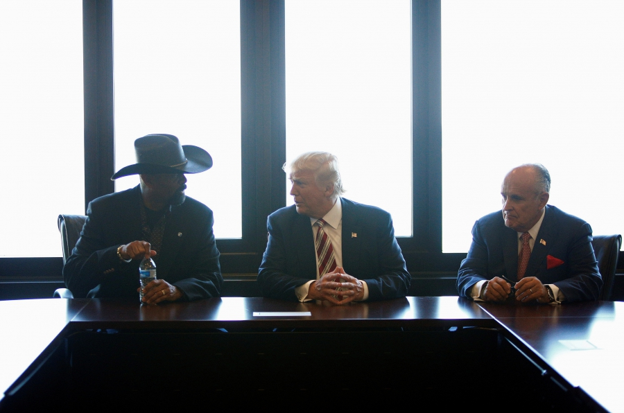 Three men at a table, one on left in cowboy hat