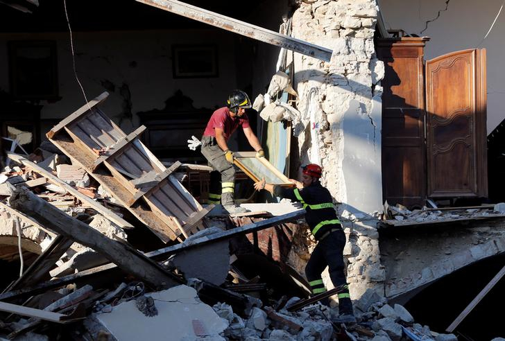 Firefighters remove a painting from a collapsed house following an earthquake in Amatrice, central Italy, August 27, 2016.