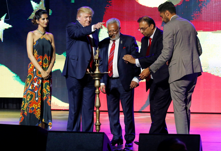 People on stage with Donald Trump, with ceremonial lamp in front.