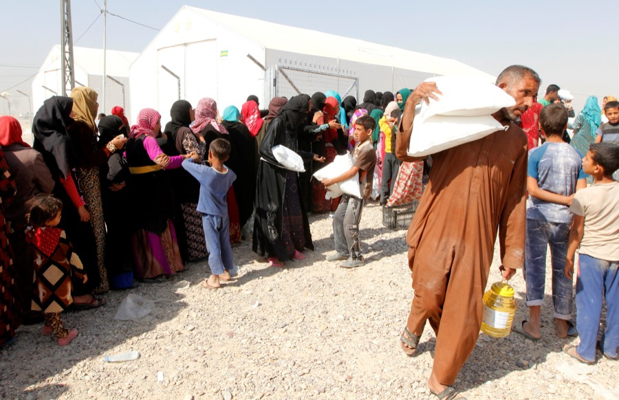 People who fled the Islamic State's strongholds of Hawija and Mosul receive aid at a camp for displaced people in Daquq, Iraq, on Oct. 13.