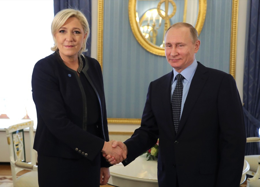 President Vladimir Putin shakes hands with Marine Le Pen
