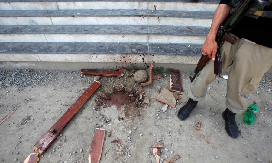 A policeman stands guard over evidence at the entry to the dorm where Mashal Khan, accused of blasphemy, was killed by a mob at Abdul Wali Khan University, in Mardan, Pakistan, April 14, 2017.