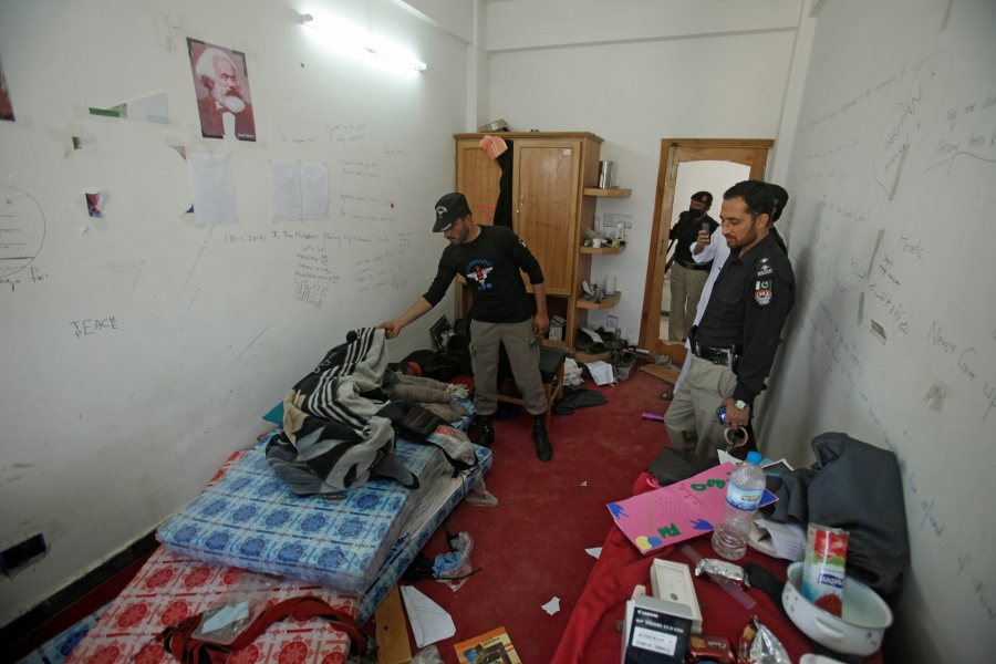 Police search the dorm room of Mashal Khan, accused of blasphemy, who was killed by a mob at Abdul Wali Khan University in Mardan, Pakistan, April 14, 2017.