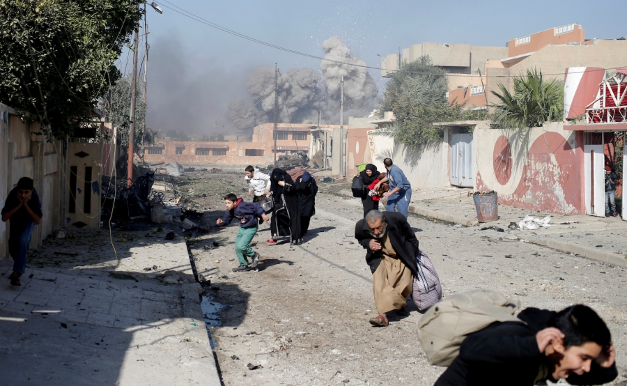 People run in panic after a coalition airstrike hit ISIS positions in the Tahrir neighborhood of Mosul, Iraq