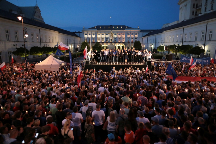 People attend candlelit rally against supreme court legislation in front of the Presidential Palace in Warsaw, Poland