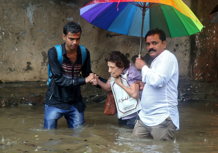 A woman is helped to move through a water-logged road after rains in Mumbai.