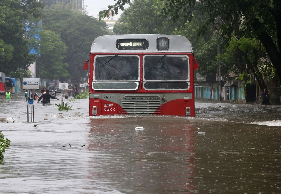 A passenger bus moves through a water-logged road during rains in Mumbai.