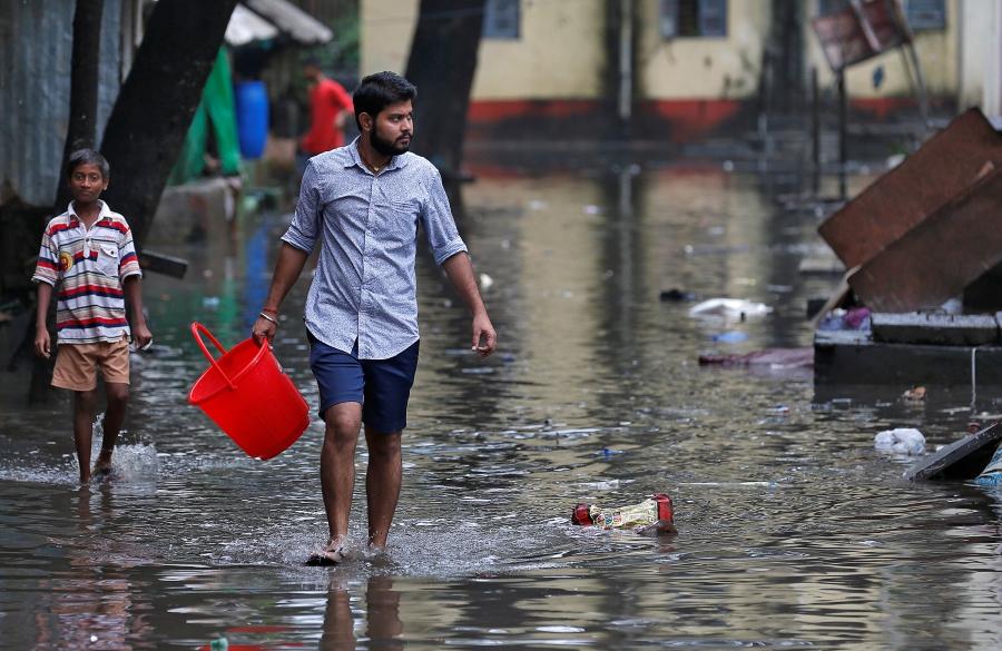 A man carrying a bucket walks through a water-logged neighbourhood in Mumbai.