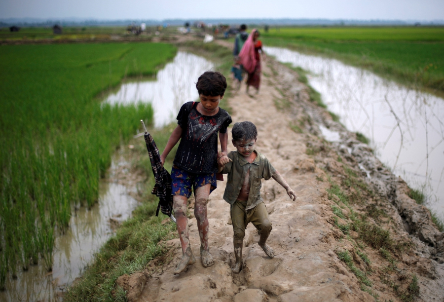 Rohingya refugee children walk on a muddy path after crossing the Bangladesh-Myanmar border, in Teknaf, Bangladesh, Sept. 6, 2017.
