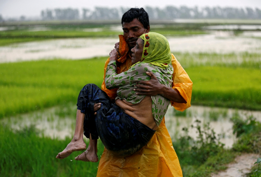 A local man in Teknaf, Bangladesh, carries an elderly Rohingya refugee woman as she is unable to walk after crossing the border from Myanmar
