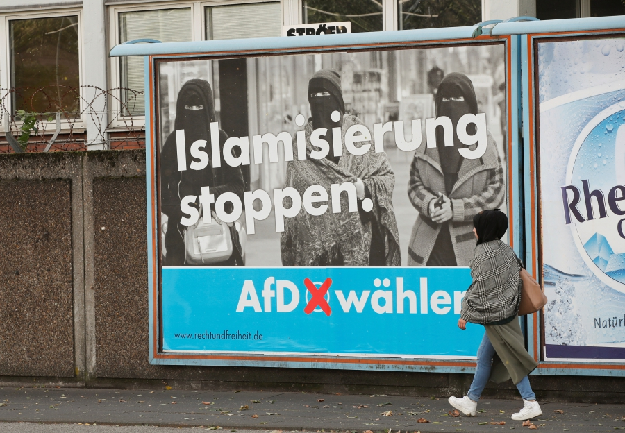 """A woman walks past an AfD election campaign poster that reads, """"Stop Islamization,"""" in Marxloh, Germany, Sept. 13, 2017."""