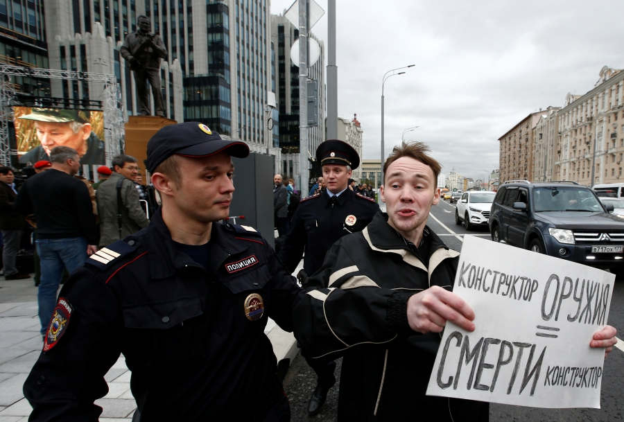 "A man is detained by police officers at the unveiling of the Kalashnikov statue on Tuesday. His sign reads: ""A weapon designer is equal to a designer of death."""