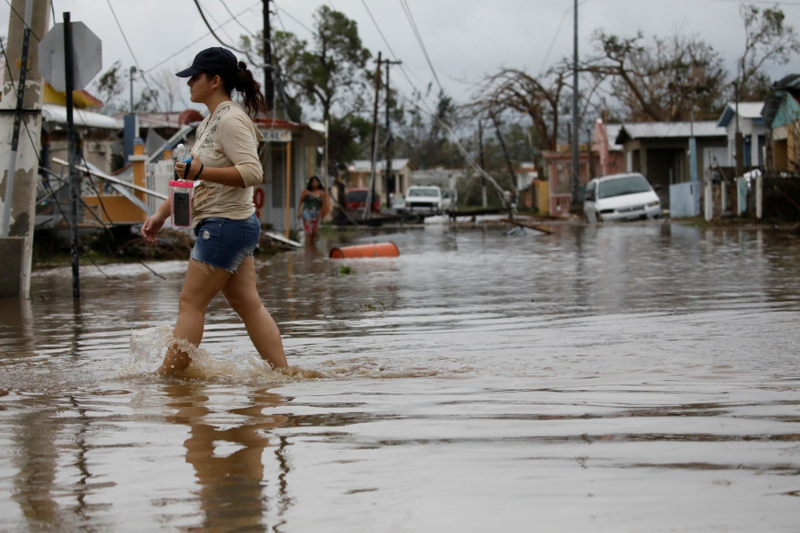 A woman wades through a flooded street after the area was hit by Hurricane Maria in Salinas, Puerto Rico, Sept. 21, 2017