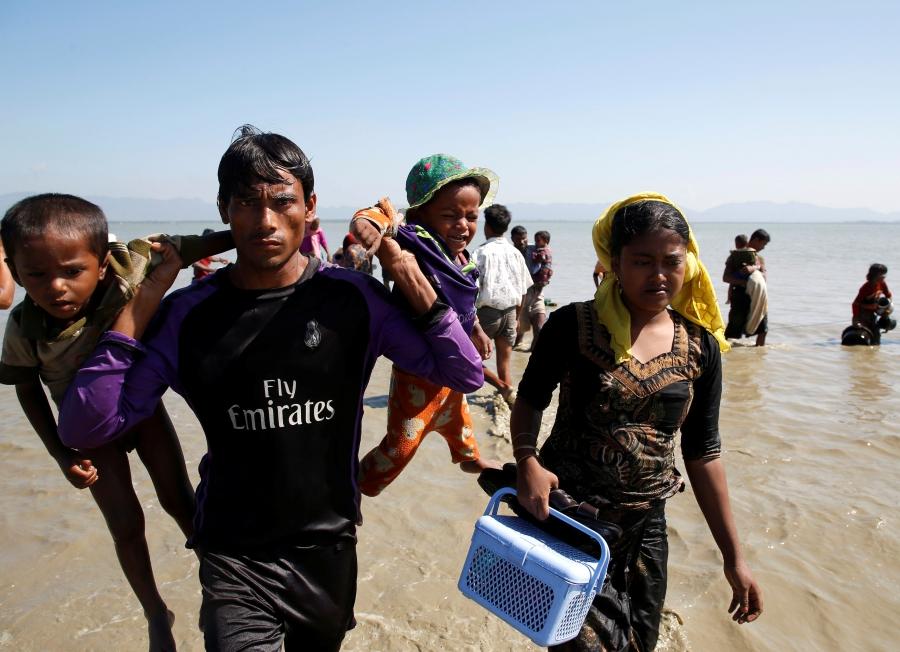 A Rohingya refugee man holding children walks towards the shore