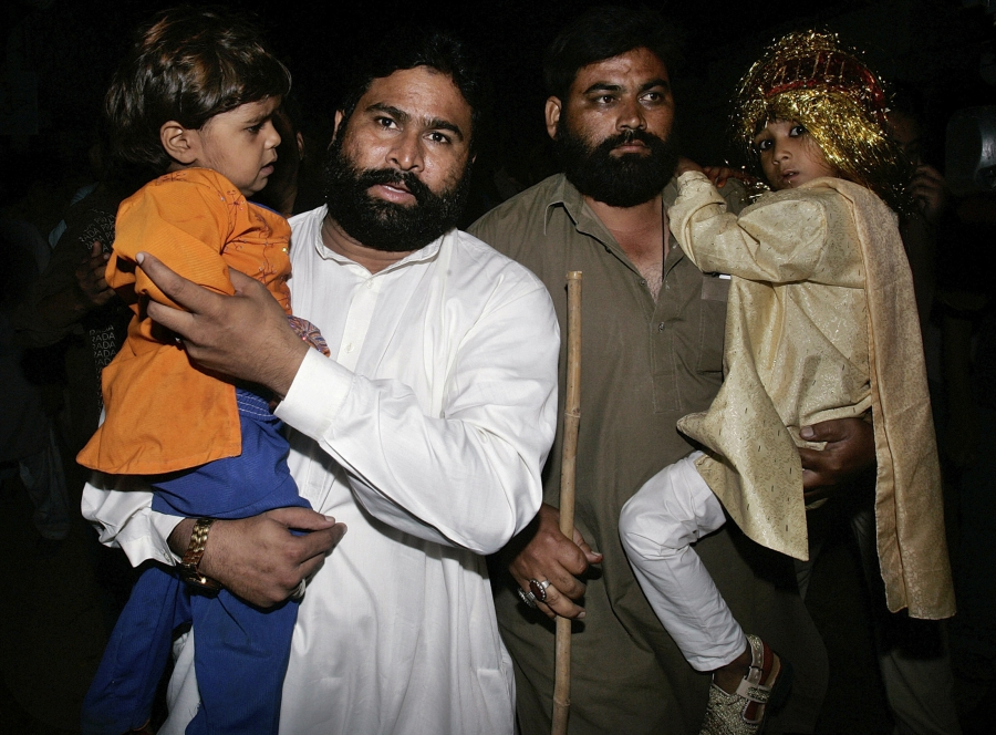 Seven-year-old groom Mohammad Waseem (R) and his 4-year-old bride Nisha (L) are escorted by security officials at a police station in Karachi after Pakistani police raided a child marriage ceremony and arrested a cleric who was presiding over the wedding,