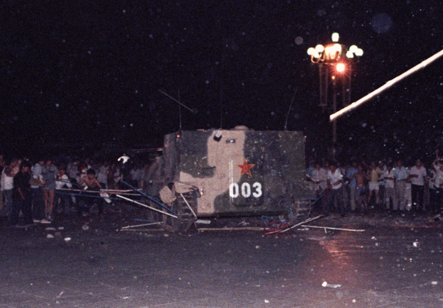 An armored personnel carrier crushes one of the tents set up on Tiananmen Square by pro-democracy protestors early Sunday morning June 4, 1989. Students were later able to set fire to the vehicle before troops entered the square and opened fire.