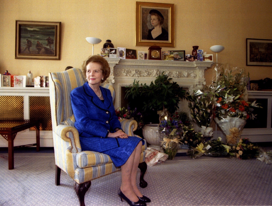 Former Prime Minister Margaret Thatcher sits at home for a 70th birthday photograph amidst floral greetings October 13, 1995.