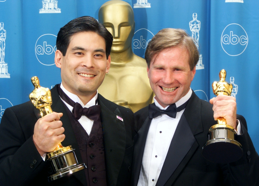 Two men in tuxedos show their Oscars statues to the cameras.