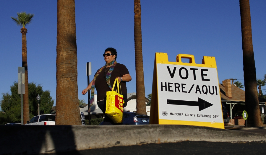 Woman walks past voter sign
