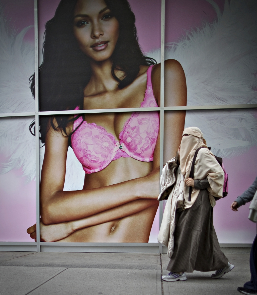A Muslim woman wearing a niqab face veil walks past a lingerie advertisement in downtown Vancouver, British Columbia.