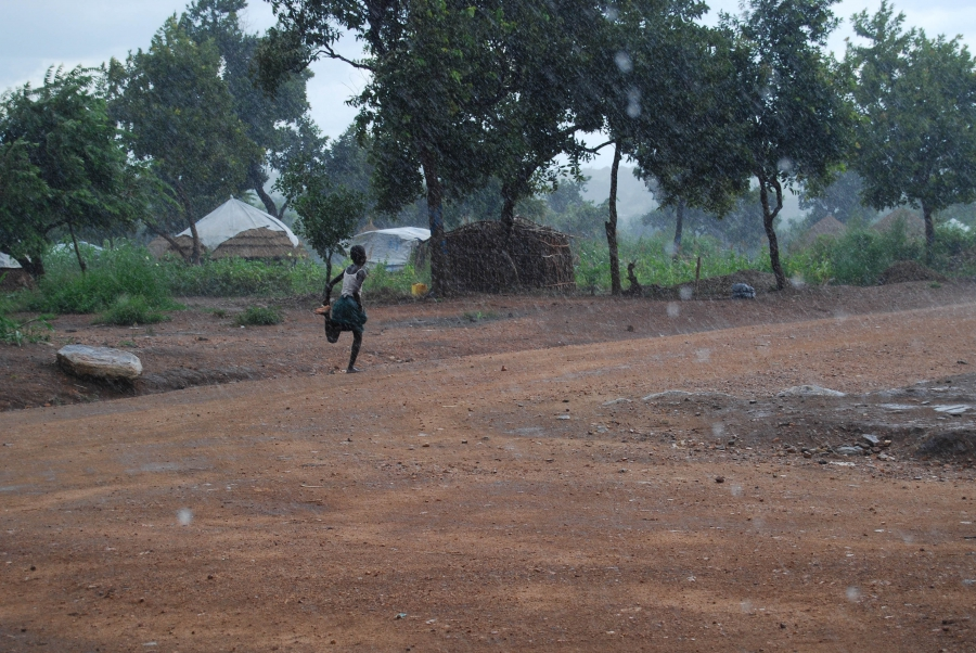 A girl runs through an afternoon rainstorm in Bidi Bidi. The rains, which come daily during certain times of the year, can flood the refugee settlement's dirt roads.