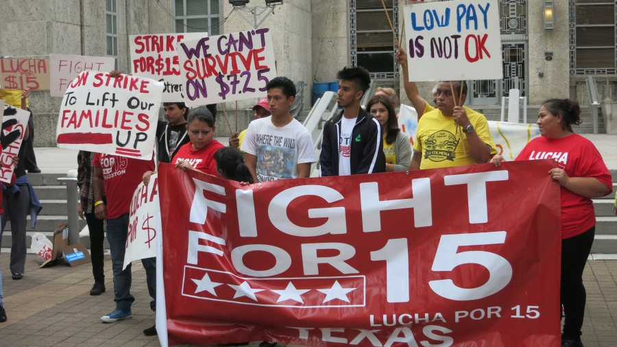 Mario Sidonio, left, and Daniel Meza standing behind a sign at a Houston rally for a $15 an hour minimum wage.