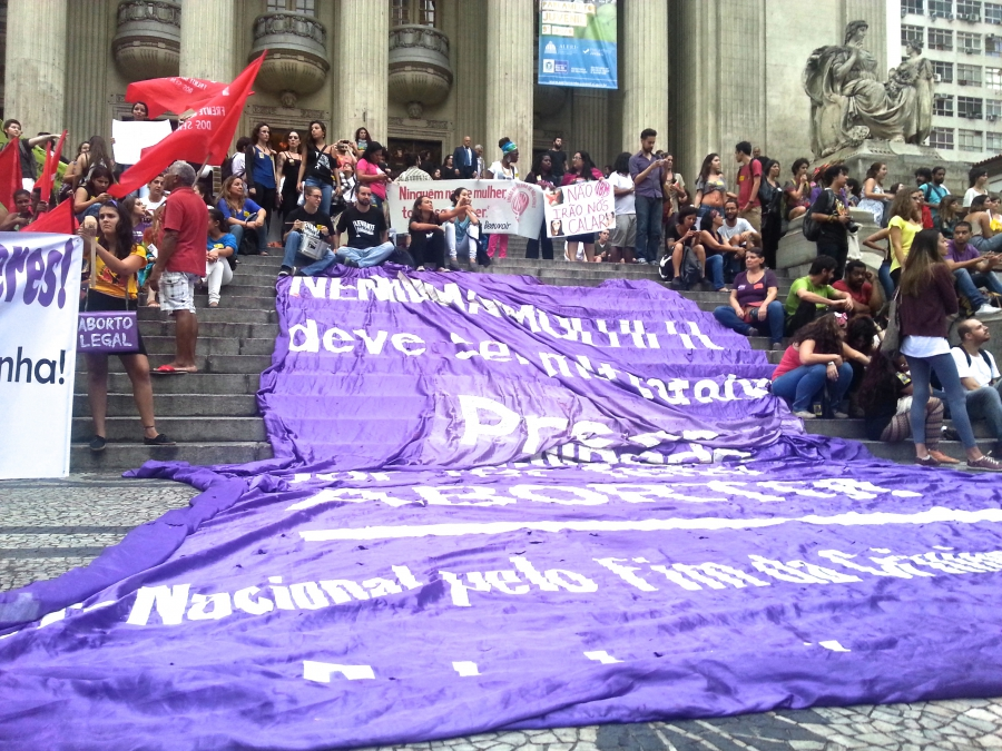 "A banner draping the front steps of Rio's state legislature reads ""No woman should be mistreated, arrested, or humiliated for having had an abortion"""