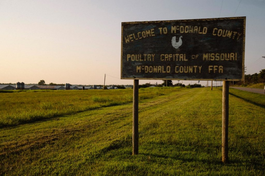 A county welcome sign stands near the Simmons Foods chicken processing plant in Southwest City, Missouri.