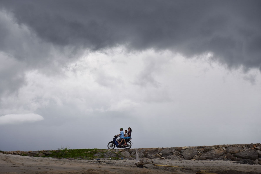 A man, child and woman ride a motor bike near the beaches of Pulau Weh island, Indonesia.