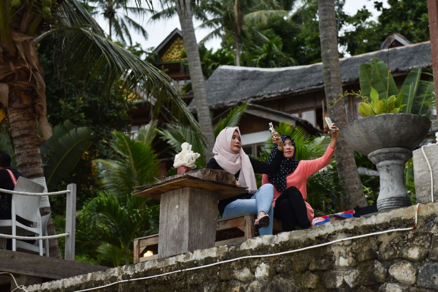 Women in hijab take selfies on their mobile phones at Casa Nemo Resort and Spa.