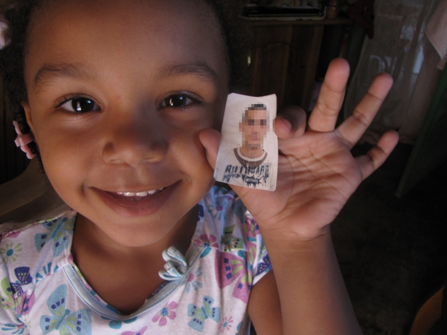 Sasha Barrios holds up a picture of the Uruguayan marine her mother says is Sasha's father. The man was a member of MINUSTAH, the UN peacekeeping for in Haiti.