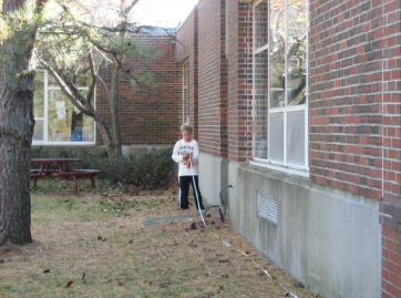 A boy with measuring tape next to brick building