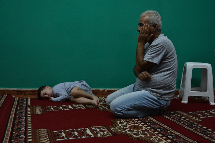 Mohammad, a 5-year-old boy from Syria, takes a nap before the night prayer on the floor of a makeshift mosque in the Attiki neighborhood in Athens.