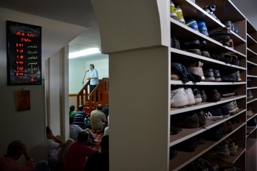 An imam is preaching moments before the Jumu'ah (Friday prayer) begins at a makeshift mosque in Metaxourgio.