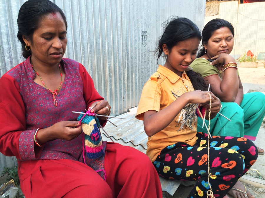 Shreesha Duwal (middle) knits with her mother (left) outside the shack where they now live. They sell the gloves they knit to make extra money.