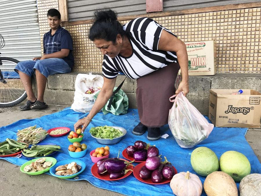 Sunila Wati sets her produce out on a tarp on the sidewalk hoping for customers